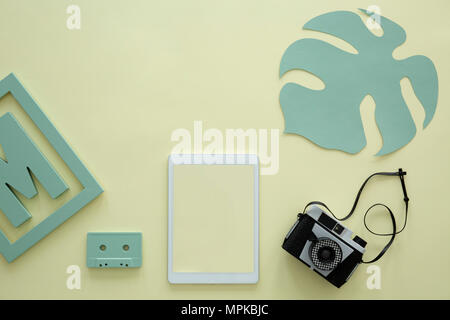 Mockup of tablet on yellow background with camera, green leaf and cassette - Stock Photo