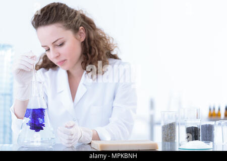 Chemist pouring substance into a flask with solution in the laboratory - Stock Photo