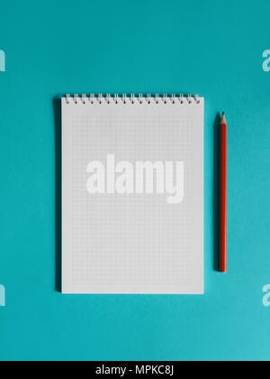 School supplies photo Notebook and red pencil are lying on the blue desk Photo mock up in minimalist style with copy space - Stock Photo