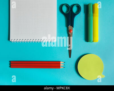 School supplies photo Notebook, stationery scissors, markers, pencils and stickers are lying on the blue desk - Stock Photo