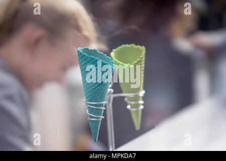 Light background with two empty bright wafer cornets for ice cream on stand, real blurry real scene. Selective focus. Service, catering concept - Stock Photo