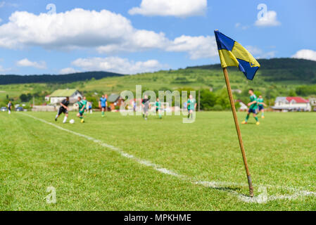 Retro corner flag on the foreground of amateur soccer field, football players fighting for the ball on the blurry background - Stock Photo
