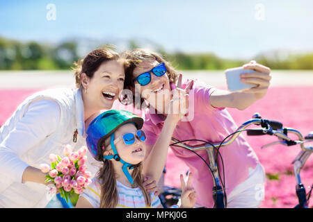 Dutch family riding bicycle in tulip flower fields in Netherlands. Mother and kids taking selfie picture with mobile phone camera on bikes at blooming - Stock Photo