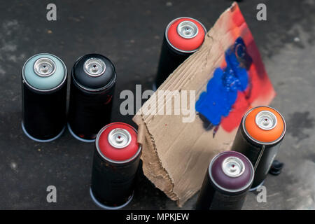 Aerosol cans of spray paint and cardboard palette for paint, graffiti on a dark background of asphalt. Top view. Urban contemporary iconic culture of street youth - Stock Photo