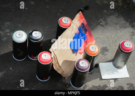 Aerosol metal cans of spray paint and cardboard palette for paint, graffiti on dark background of asphalt. Urban contemporary iconic culture of street youth - Stock Photo