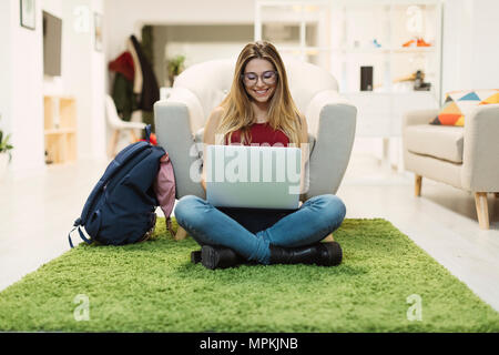 Casual young woman using laptop in coworking space - Stock Photo