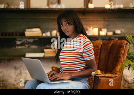 Portrait of young woman sitting on an old leather chair working on laptop in a loft - Stock Photo
