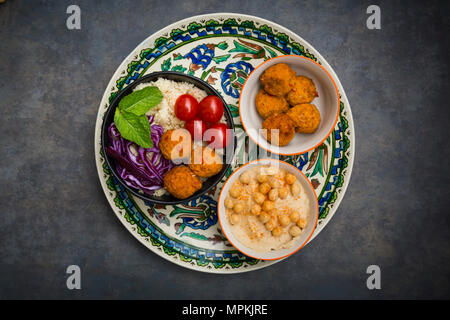 Couscous sweet potato falafel bowl with red cabbage, tomato, mint and hummus - Stock Photo