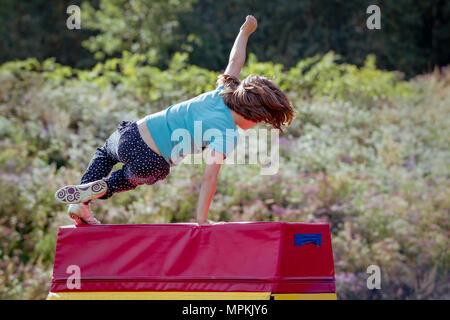 Girl Child Practicing (Practising) Gymnastics Outside on Vaulting Horse - Stock Photo