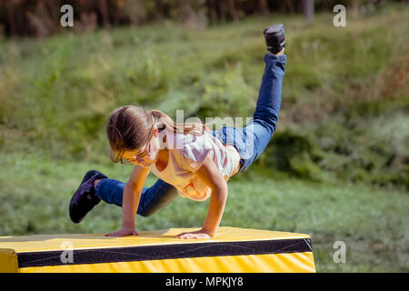 Girl Child Practicing (Practising) Parkour Gymnastics Outside on Vaulting Horse - Stock Photo