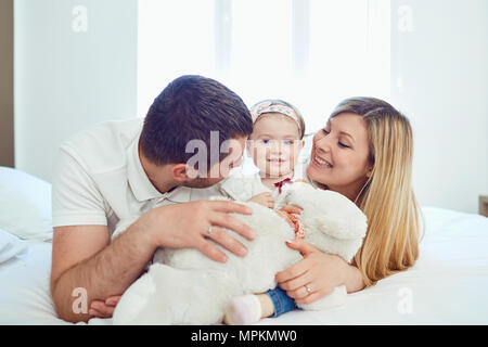 Happy family lying on bed in bedroom - Stock Photo