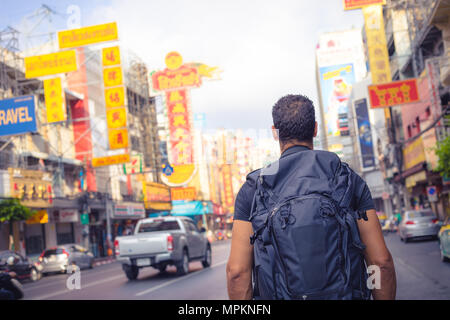 men backpacker looking at the famous place of Yaowarat road in Chinatown Bangkok during day, Thailand , Southeast asia . - Stock Photo