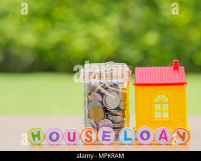 Coins in jar with red house. Saving for home concept - Stock Photo