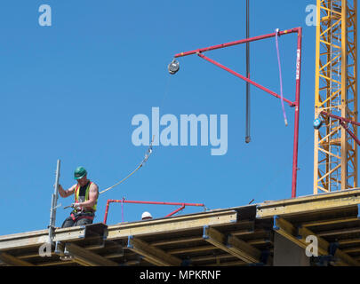 A building construction worker wearing a safety harness attached to an Alsina Fall Arrest System, England, UK - Stock Photo