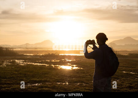 silhouette of a woman holding a smartphone taking pictures outside during sunrise or sunset. - Stock Photo