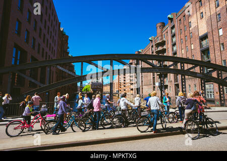 HAMBURG, GERMANY - May 5, 2018: Bicycling tour in old Speicherstadt near Wandrahmsfleet house in Hamburg. - Stock Photo