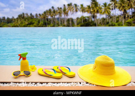 Swimming pool accessories flat lay. Top view of beach items on infinity pool deck. Flip flops, bikini and hat, sun glasses. Water toys. Summer vacatio - Stock Photo