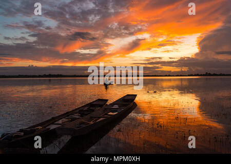 Sunset view in rural with silhouette of a man in small boat and  two small boats parking on the river in rural of Thailand - Stock Photo
