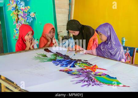 Krabi, Thailand - May 2, 2015: Cute Muslim girls wearing black and purple hijab painting pattern on Batik fabric in her home in Krabi, Thailand - Stock Photo