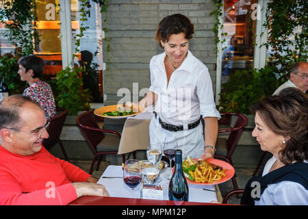 Quebec City Canada Lower Town Rue du Sault au Matelot L'Echaude Restaurant alfresco dining waitress serves food - Stock Photo
