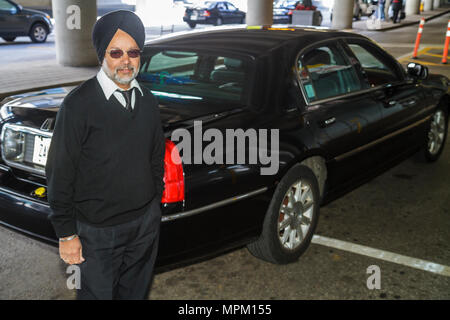 Toronto Canada Ontario Lester B. Pearson International Airport YYZ transportation limousine driver chauffer job Asian man turban - Stock Photo