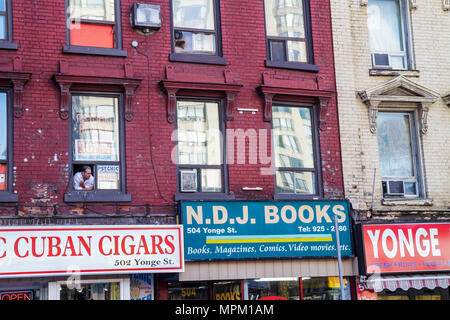 Toronto Canada Ontario Yonge Street red brick dilapidated building man looking out window Tabac Cuban Cigars tobacco French word - Stock Photo