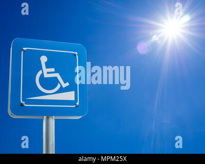 Disabled parking space and wheelchair way sign and symbols on a pole warning motorists - Stock Photo