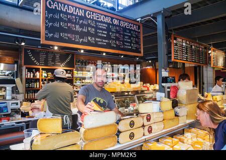 Toronto Canada Ontario St. Lawrence Market shopping vendor merchant cheese shop aged cheddar blackboard special counter man woma - Stock Photo