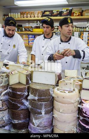 Toronto Canada Ontario St. Lawrence Market shopping vendor merchant cheese shop man sales clerk employee cheese wheel chef coat - Stock Photo