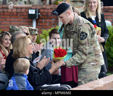 Sgt Brian Lehfeld, HHC, 296th Brigade Support Battalion, hands flowers to the outgoing commander's mother, Mrs. Judy Zimmer while wife Jodi Zimmer and LTC Zimmer's children Joseph, Jack, and Jewel look on during a Change of Command ceremony 24 March, 2017 on Watkins Field. - Stock Photo