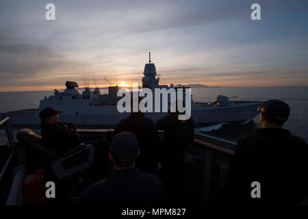 170326-N-ZE250-246   FIRTH OF CLYDE, United Kingdom - (March 26, 2017) – The Royal Netherlands Navy frigate HNLMS De Ruyter (F804) conducts replenishment-at-sea approaches with USS Carney (DDG 64) during Exercise Joint Warrior 17-1 March 26, 2017. Carney, an Arleigh Burke-class guided-missile destroyer, forward-deployed to Rota, Spain, is conducting its third patrol in the U.S. 6th Fleet area of operations in support of U.S. national security interests in Europe. (U.S. Navy photo by Mass Communication Specialist 3rd Class Weston Jones/Released) - Stock Photo