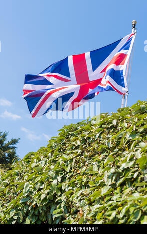 Union Jack flag of United Kingdom of Great Britain and Northern Ireland, flying on a pole at the front of a house in England, UK. - Stock Photo
