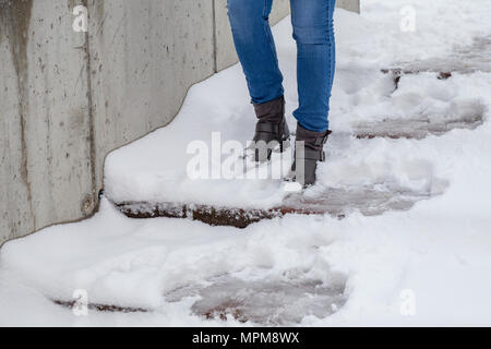 Female legs wearing boots going down the stairs on snowy pathway at winter. - Stock Photo