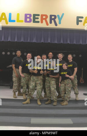 The 82nd Airborne Division rock band, Riser Burn, pictured from left to right: Spc. DGiovhani Denize, Spc. Chris Deroche, Sgt. 1st Class Kevin Quinones, Staff Sgt. Tony Buzzella, Spc. Andrews Santana, Staff Sgt. Traci Gregg, Sgt. Patrick O'Hara, Spc. Rachel Watson, Staff Sgt. Gunnar Kalstrom, after a concert for the children of Gallberry Farm Elementary School in Fayetteville, N.C., March 7, 2017, in honor of Music In Our Schools Month. The annual March celebration engages music educators, students and communities to promote the benefits of high quality music education programs in schools. (U. - Stock Photo