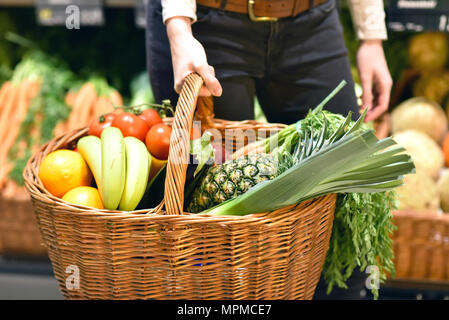 grocery shopping in the supermarket - filled shopping trolley with fresh fruit and vegetables - Stock Photo