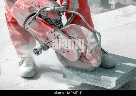Worker cutting marble tile with electric hand saw at construction site. - Stock Photo