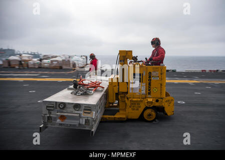 170330-N-WF272-484  EAST CHINA SEA (March 30, 2017) Aviation Ordnanceman 3rd Class Austin Hoffman transports ordnance on the flight deck of the amphibious assault ship USS Bonhomme Richard (LHD 6) during a replenishment-at-sea. Bonhomme Richard is on a routine patrol operating in the Indo-Asia-Pacific region to enhance warfighting readiness and posture forward as a ready-response force for any type of contingency. (U.S. Navy photo by Mass Communication Specialist 2nd Class Diana Quinlan/Released) - Stock Photo