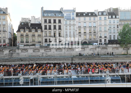Tourist boat with people tourists sitting on deck passing a row of terraced buildings and quai along River Seine in Paris France EU  KATHY DEWITT - Stock Photo