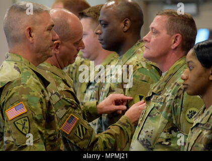 Georgia Army National Guard Col. Alan B. Alexander, commander of the 122nd Tactical Support, places the shoulder sleeve insignia of the 7th Infantry Division on the sleeve of Capt. Terrell Wood during a patch changing ceremony at the Clay National Guard Center, Marietta, Ga., April 1, 2017. - Stock Photo