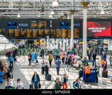 Passengers in busy main concourse, Waverley Railway Station, Edinburgh, Scotland, UK with breaking news headline on giant TV screen - Stock Photo