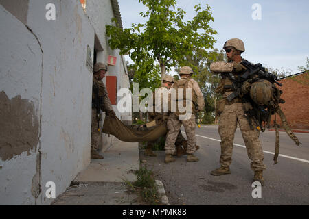 """U.S. Marines and a Navy Corpsman assigned to Special Purpose Marine Air Ground Task Force-Crisis Response-Africa carry a simulated casualty out of a building during a bilateral Military Operation on Urbanized Terrain exercise at Spanish 2nd Special Operations Group """"Granada"""" members in Alicante, Spain, March 30, 2017. The exercise provided an opportunity for Marines and Spanish SOF members to improve interoperability, maintain joint readiness and strengthen relationships. (U.S. Marine Corps photo by Sgt. Jessika Braden) - Stock Photo"""