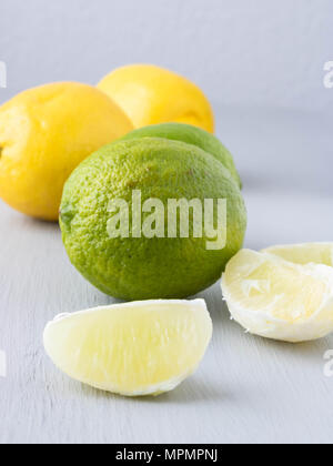 LIme, lime segments and lemons against wooden background, colorful citrus fruits - Stock Photo