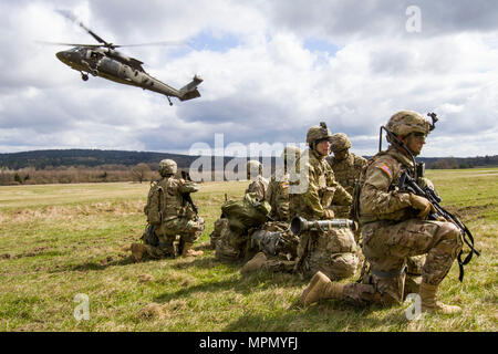 A UH-60 Black Hawk helicopter from A Company, 2-10 Assault Helicopter Battalion, arrives at the pickup zone at Grafenwoehr Training Area, Germany, on April 6. The aviators were taking part in part of a joint-training exercise with Soldiers from 3rd Squadron, 2nd Cavalry Regiment, in anticipation of working together during future Atlantic Resolve missions. (U.S. Army photo by Spc. Thomas Scaggs) 170406-A-TZ475-151 - Stock Photo