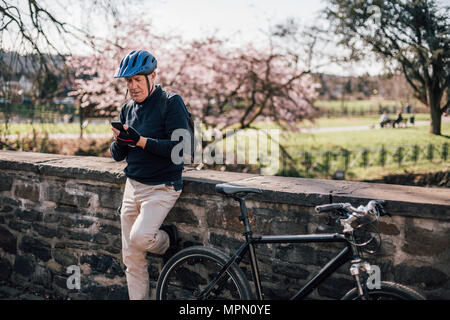 Senior man with cycling helmet using smartphone - Stock Photo