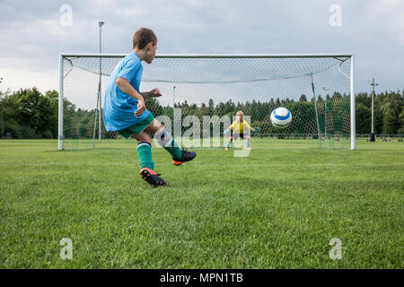 Young football player kicking ball in front of goal with goalkeeper - Stock Photo