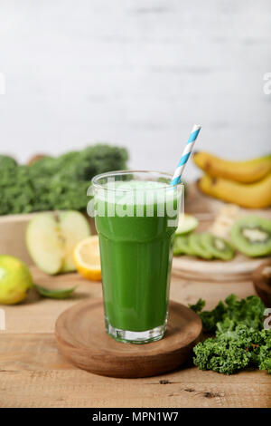 Green smoothie surrounded by ingredients - Stock Photo