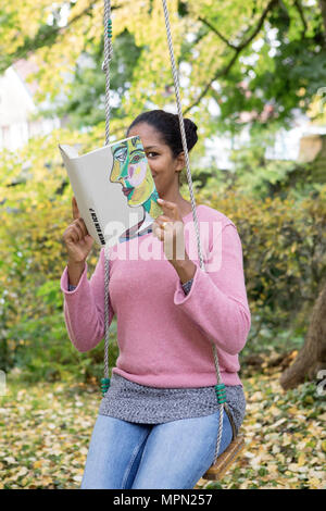 Woman covering face with book, reading poetry in a garden - Stock Photo