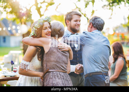 Guests congratulating bride and groom at wedding reception outside in the backyard. - Stock Photo