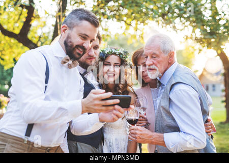 Bride, groom and guests with smartphones taking selfie outside at wedding reception. - Stock Photo