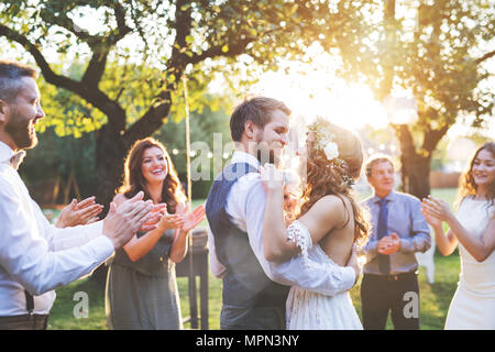 Bride and groom dancing at wedding reception outside in the backyard. - Stock Photo